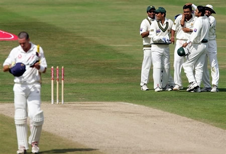 Kevin Pietersen walks back to the Pavilion as Pakistan players congratulate Danish Kaneria
