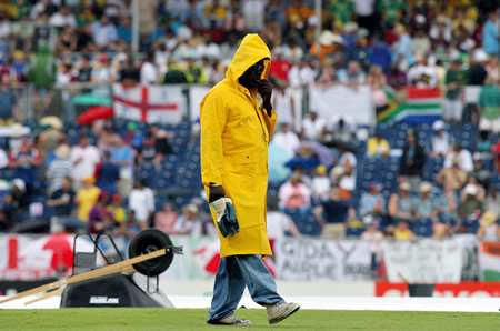 A groundsman walks past the covered crease under a rainfall
