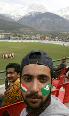 A fan with face painted with the national flags of India and Pakistan