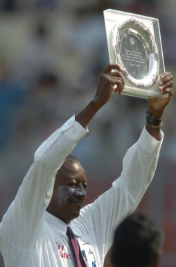 Umpire Steve Bucknor holds a memorial plaque