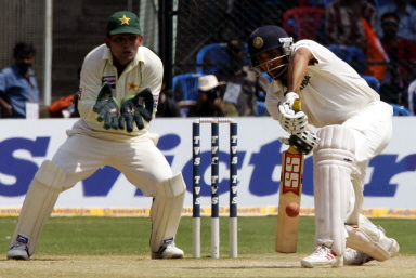 VVS Laxman hits a ball to the boundary as Kamran Akmal looks on