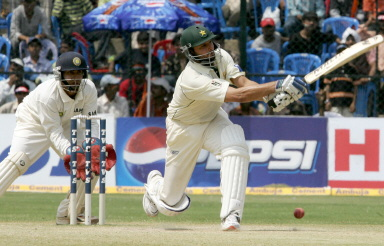 Shahid Afridi watched by Dinesh Karthik as he plays a shot