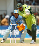 Abdul Razzaq plays a stroke as Mahender Dhoni looks on