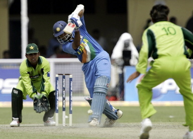 Acting captain Rahul Dravid is watched by Kamran Akmal