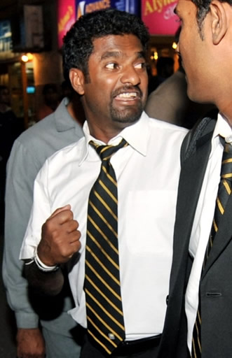 Muralitharan walks out with teammates following the team's arrival in Karachi