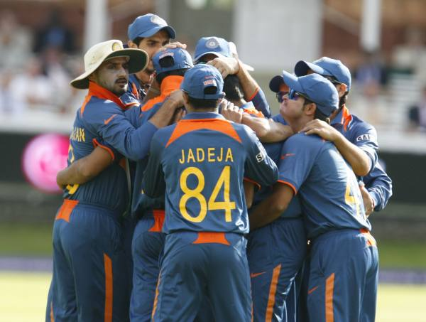 The Indian team huddles after a wicket