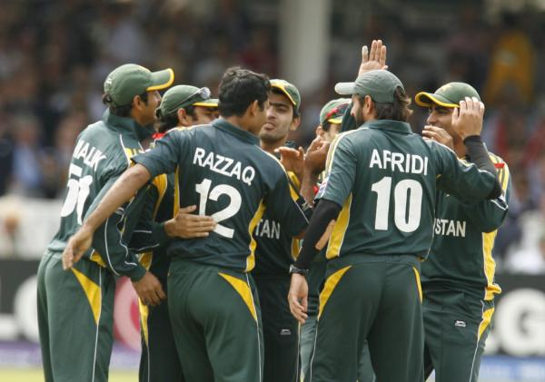The Pakistani team celebrates the fall of a wicket