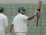 Nasir Hossain raises his bat after reaching his half-century