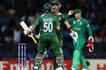 Saeed Ajmal and Umar Akmal embrace each other after scoring a four to finish the match