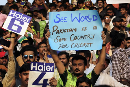 A Pakistan cricket fan holds up a poster
