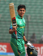 Umair Masood raises his bat after scoring a century