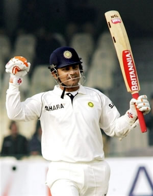 Virender Sehwag waves his bat after his 200 runs