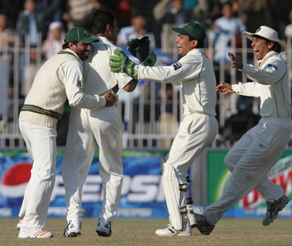 Pakistan players celebrate the wicket of Sehwag.