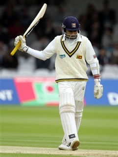 Jayawardene raises his bat after his 50