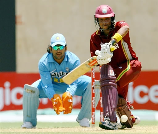 Sarwan slams a shot as Dhoni looks on