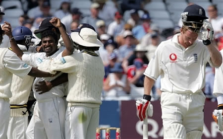 Muralitharan celebrates as Collingwood walks back to the pavilion